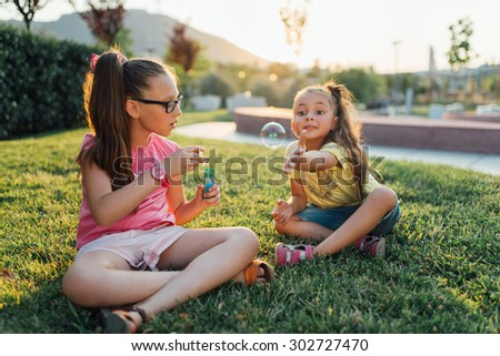 Two girls are sitting on the grass in the park