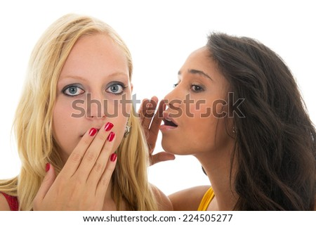 Two girls are talking secrets to each other isolated over white background