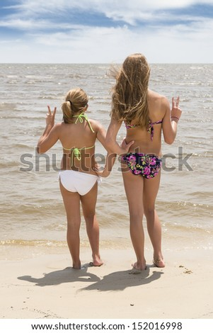 Two girls at beach looking at water - stock photo