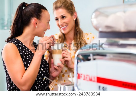Two girls, best friends, drinking latte macchiato in cafe or coffee bar