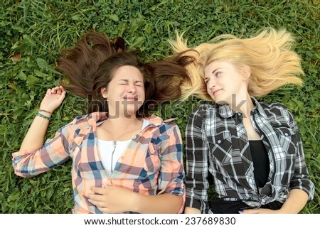 Two girls blonde and brunette friends are lying on grass - stock photo