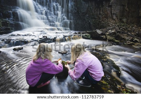 Two girls by a waterfall, Vastergotland, Sweden.