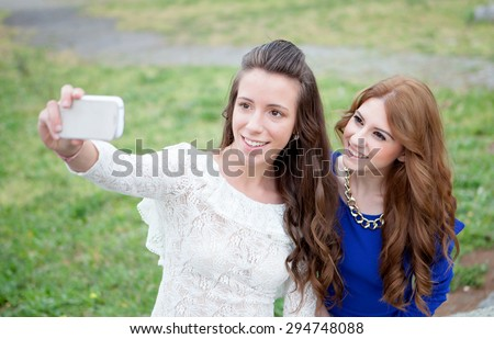 Two girls by becoming a photo with the phone in the park for upload to social networks - stock photo