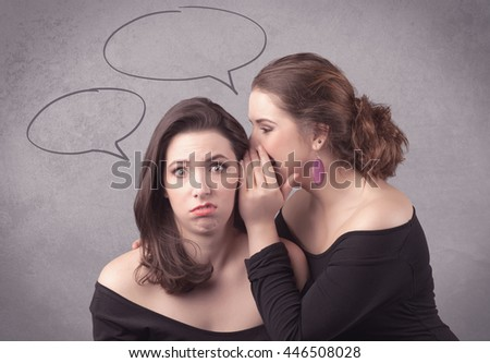 Two girls chatting and sharing their secrets concept with drawn chat bubbles on the background urban wall. - stock photo