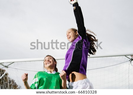 Two girls cheering in front of soccer net