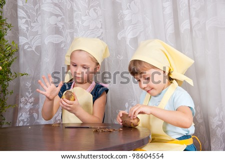 Two girls clean boiled potatoes - stock photo