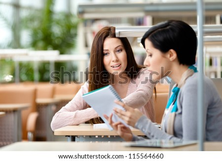 Two girls communicate sitting at the table at the reading hall. Process of communication - stock photo