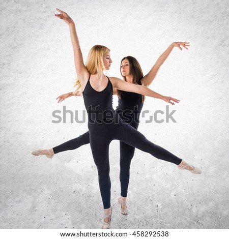Two girls dancing ballet over textured background