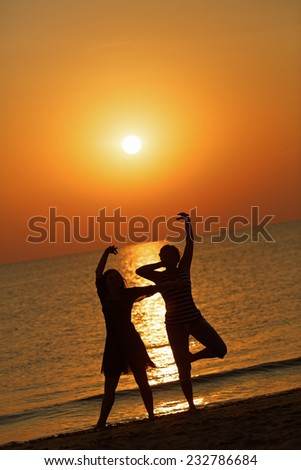 Two girls dancing on the background of the dawn. Shallow depth of field. - stock photo