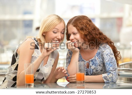 Two girls discuss men in a cafe