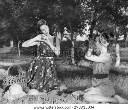 two girls do a photo at a picnic in retro style
