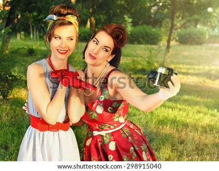 two girls do a photo at a picnic in retro style - stock photo