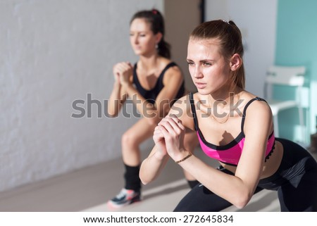 two girls doing squats together indoors training warm up at gym fitness, sport and lifestyle concept. - stock photo