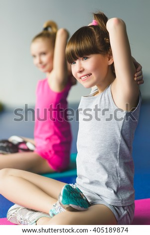 Two girls doing yoga stretching in fitness class - stock photo