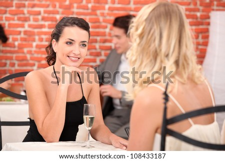 two girls dressed in robes talking in a restaurant