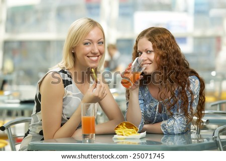 Two girls eat in fast food cafe