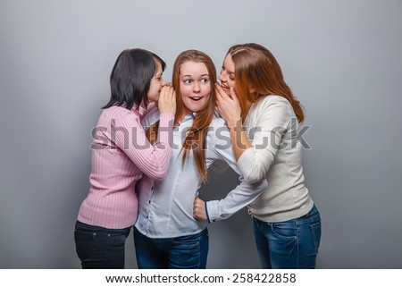 two girls European appearance blonde and brunette whispered in his ear the secret third blonde girl on a gray background - stock photo