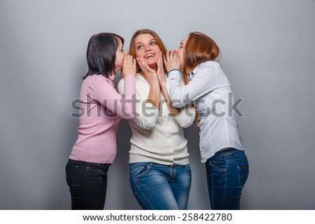 two girls European appearance blonde and brunette whispered in his ear the third the secret girl on a gray background, emotions - stock photo