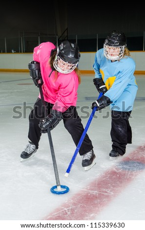 Two Girls fight for the ring, Ringette is a Canadian Ice sport played in a hockey rink or arena. - stock photo