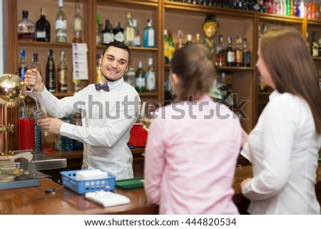 Two girls flirting with smiling young handsome barman