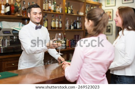 Two girls flirting with smiling young handsome barman at bar