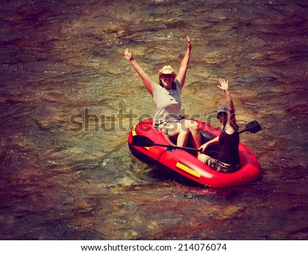 two girls floating down a river in an inflatable raft toned with a retro vintage instagram filter effect  - stock photo