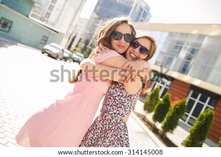 two girls friends laughing and hugging. hug and smile outdoor - stock photo