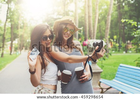 Two girls friends outdoors watching photos at digital camera. Young female tourists in boho chic fashion clothes, laighing and having fun in summer park. Travelling together, lifestyle portrait. - stock photo
