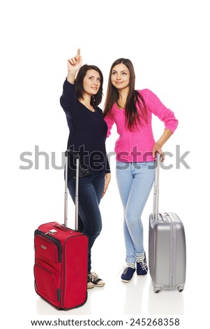 Two girls friends standing in full length with travel suitcases and pointing up to blank copy space, isolated on white background. - stock photo