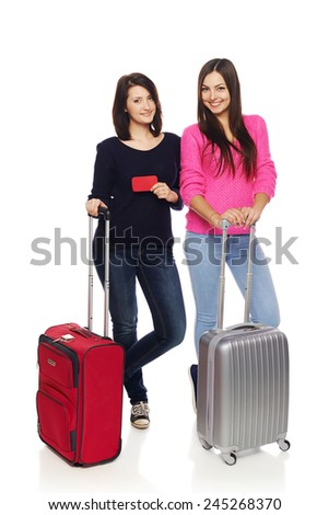 Two girls friends standing in full length with travel suitcases showing blank credit card, isolated on white background. - stock photo