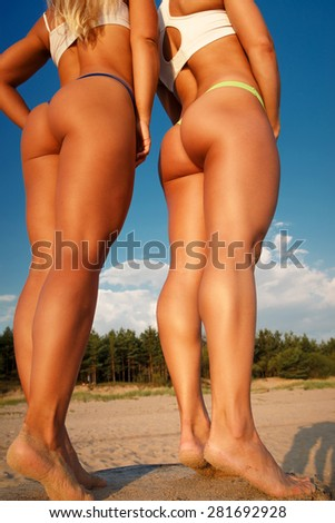Two girls from a back in sexy swimsuits on a beach under blue sky
