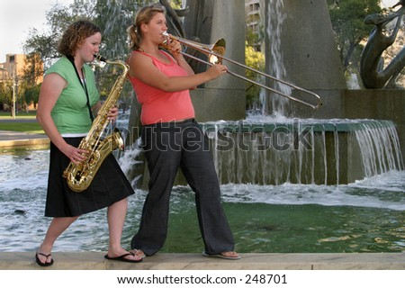 Two girls from the brass section of Final Con, band at the 'Fusion' Adelaide Christian Easter Festival, Victoria Square, 27th March, 2005 - stock photo