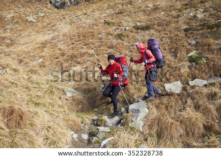 Two girls go on a mountain trail.