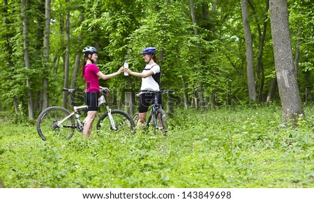 two girls having a break during cycling  in the forest