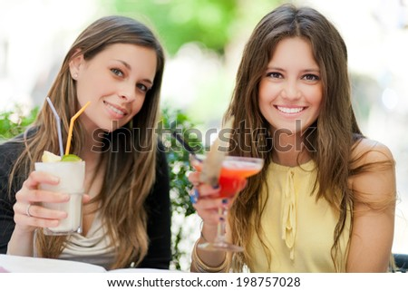 Two girls having an aperitif outdoor - stock photo