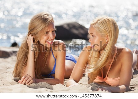 Two girls having chit-chat on the beach - stock photo