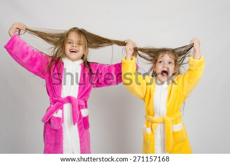Two girls having fun in dressing gowns keep wet hair