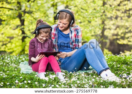 Two girls having fun in park, using digital tablet and listening music - stock photo