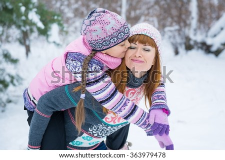 Two girls having fun in winter, winter fun outdoors. Family of mother and her adorable little daughter outdoors on beautiful winter day with snow. girls in winter forest.   - stock photo