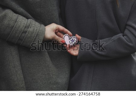 Two girls holding a heart in its hands behind spring