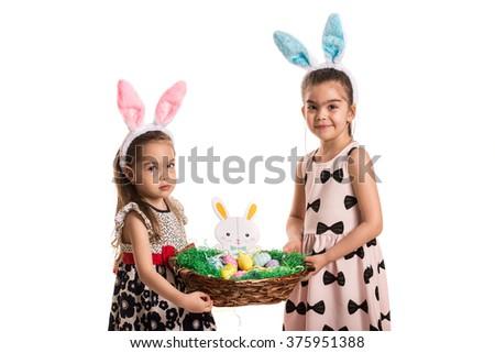 Two girls holding Easter basket isolated on white background - stock photo
