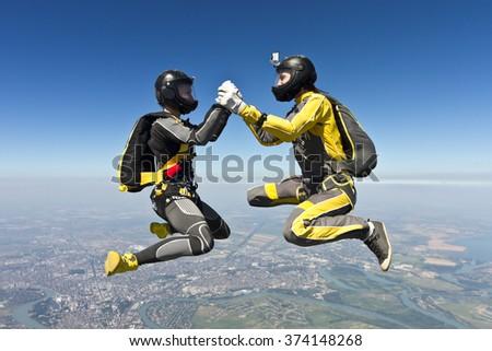 Two girls holding hands parachutist. - stock photo