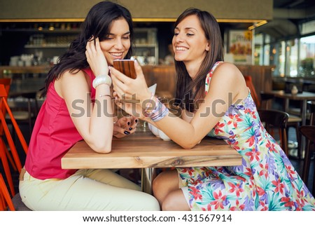 Two girls in a coffee shop, smiling, gossiping, drinking coffee
