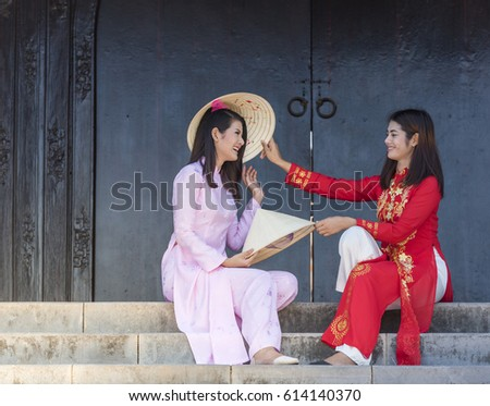 Two girls in ao dai Vietnamese's traditional costumes carry the hat sitting at the staircase in the ancient city