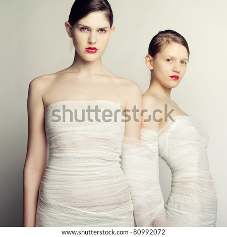 Two girls in bandages on a dark background - stock photo