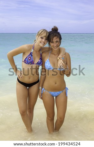 two girls in bikinis at the beach - stock photo