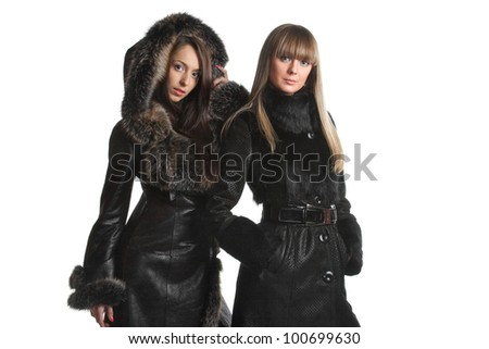 Two girls in black fur coats on a white background - stock photo