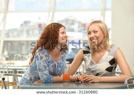 Two girls in cafe confidentially look against each other and smile - stock photo