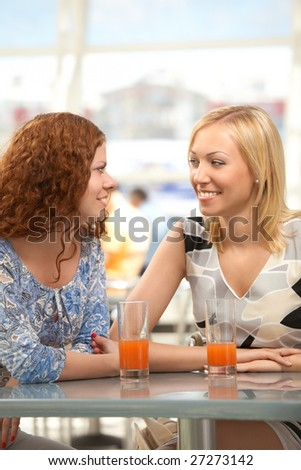 Two girls in cafe look against each other and smile - stock photo