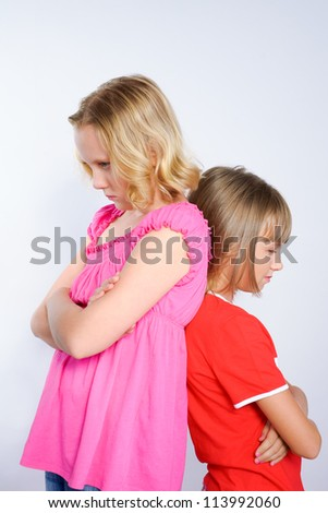 two girls in conflict standing back to back - stock photo